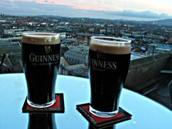 "Two ""perfectly poured"" Guinness beers atop the Guinness factory, overlooking the city of ."